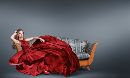 Young woman in red luxurious long red dress sitting on the sofa Foto de archivo