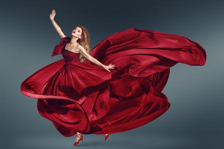 赤いロングドレスをひらひら舞うファッション女性