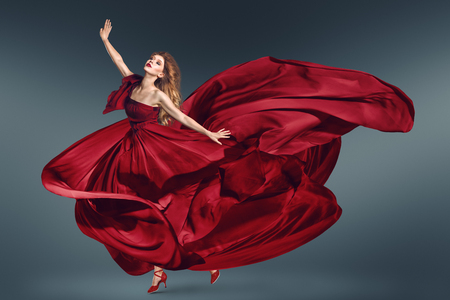 Fashion woman dancing in fluttering red long dress
