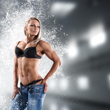 Bodybuilder atletische vrouw in bikini die haar spieren toont