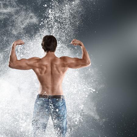 cuerpo hombre: Culturista hombre atlético muestra sus músculos con una potente explosión de nubes de polvo. Vista trasera de la parte posterior