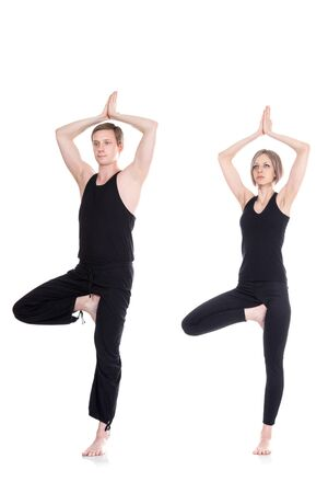tree position: Young man and woman doing yoga and meditating in tree position isolated on white background