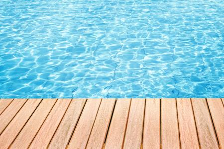 スイミング プールの水とテキストのためのスペースを持つ木製の机の抽象的なデザイン