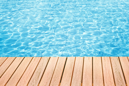 Abstract design of swimming pool water and wooden desk with space for text