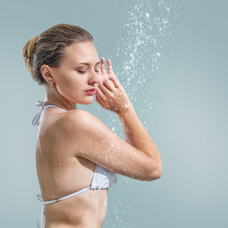 Young beautiful woman enjoying shower studio shot against gray background Stock Photo