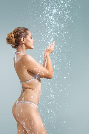 Young beautiful woman enjoying shower studio shot against gray background Stock Photo