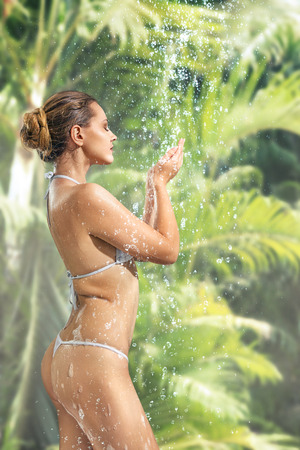 Woman enjoying shower at tropical SPA in jungle forest Stock Photo