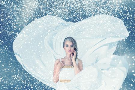 Snow winter young woman in long white dress fashion portrait