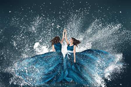 Snow winter two young dancing women in long blue dress fashion portrait