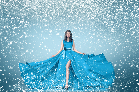 Snow winter young woman in long blue dress fashion portrait