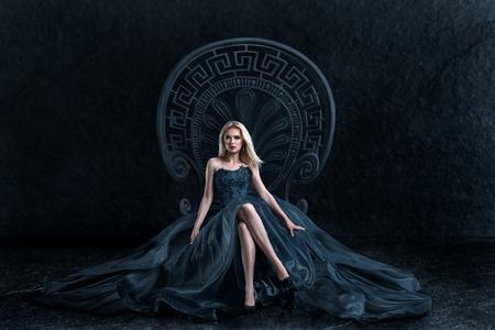 Kobieta w luksusowej sukni sukni siedzi na tronie królowej