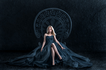 Una mujer en un vestido de traje de lujo sentado en el trono de una reina