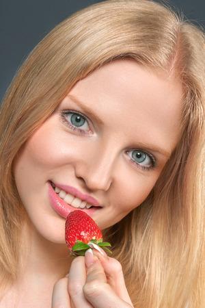 Beautiful young blonde woman eating ripe strawberry photo
