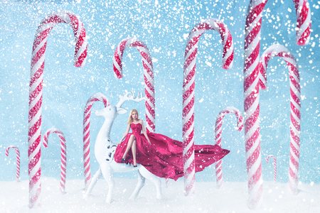 Fashion young woman riding on the deer in Christmas candy peppermint cane forest with snowfall against blue snow frost background