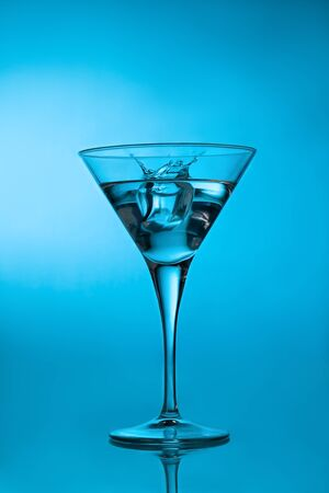 Ice cube splashing martini cocktail in a glass over blue background