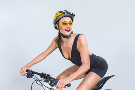 Beautiful young woman riding on bicycle isolated over white background