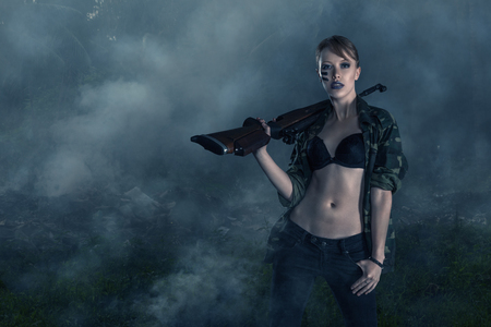 Apocalyptic portrait of young sexy woman warrior against of jungle forest in fire