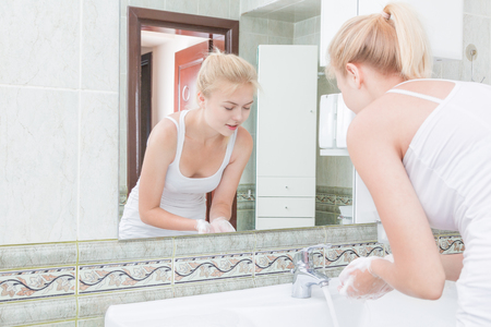 manos limpias: Mujer joven que se lava la cara y las manos con agua limpia en el baño