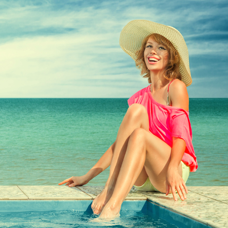 Young woman sun bathing in tropical spa resort swimming pool Stock Photo