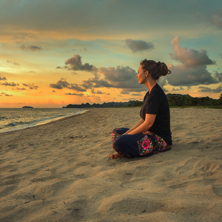 Woman sitting on beach sand doing yoga meditating and relaxing at sunset time photo