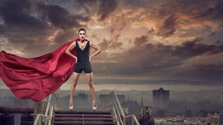 Portrait of young hero woman with super person red cape Stock Photo - 78223493