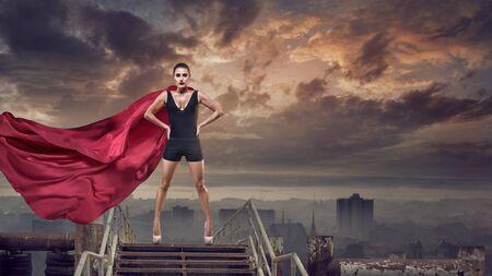 Portret van jonge held-vrouw met super persoon rode cape Stockfoto