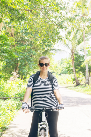Young woman travel on bicycle on country road photo