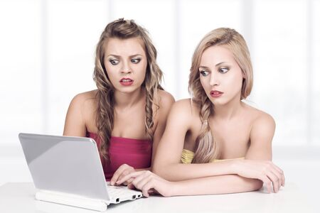 Two young emotional women working with computer and chatting in social network photo