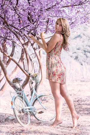 Young woman with retro bicycle in fantasy pink forest - outdoor portrait photo
