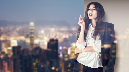 Young fashion model smoking on balcony at night asian city illuminated street photo