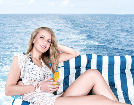 Young blonde woman enjoying sea cruise on the yacht desk photo