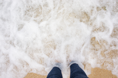 Woman standing barefoot in tropical sea water. Point of view above photo