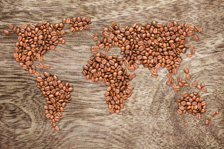 shaped: Roasted coffee beans shaped earth globe map on wooden background