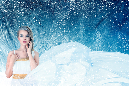 Winter fantasy fashion portrait of young attractive woman over snowy Christmas background Stock Photo