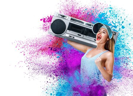 Happy young woman listening music with boombox against powder explosion background
