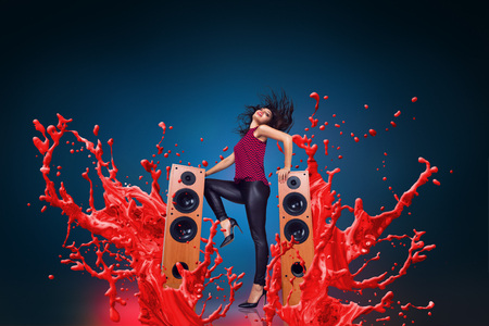 Happy young woman listening music with loud speakers in front of liquid splash explosion background 写真素材
