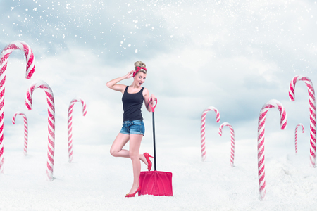 Classic sexy pin-up girl in shorts with red shovel cleaning snow in fantasy christmas place