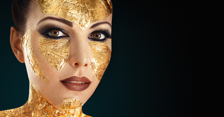 Young woman face with gold make-up mask isolated on white background Stock Photo