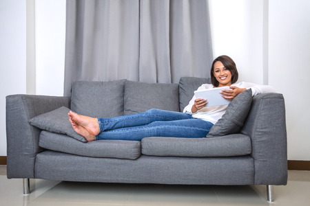 Young woman working with tablet sitting on sofa. Indoor portrait