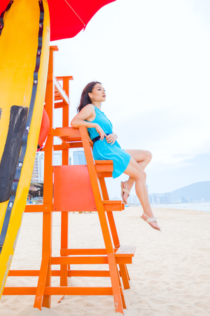 Young asian woman sitting on beach lifeguard tower and looking away