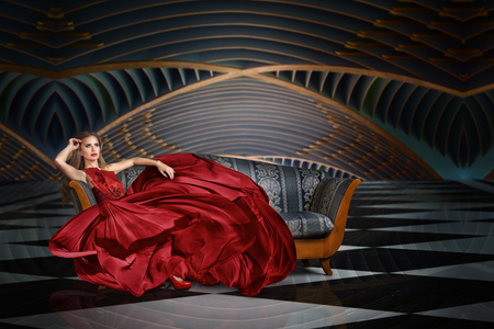 Fashion portrait of beautiful woman in long dress sitting on sofa Stok Fotoğraf