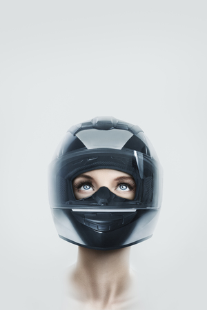 Portrait of young beautiful woman in motorcycle helmet isolated over white background with copy space above 免版税图像