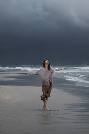 Young woman walking on the storm sea beach at rainy day in front of heavy dark cloud