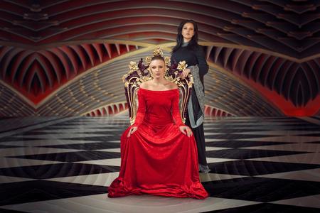 Una mujer con un vestido lujoso sentada en el trono de una reina, otra de pie detrás de ella con un vestido largo negro