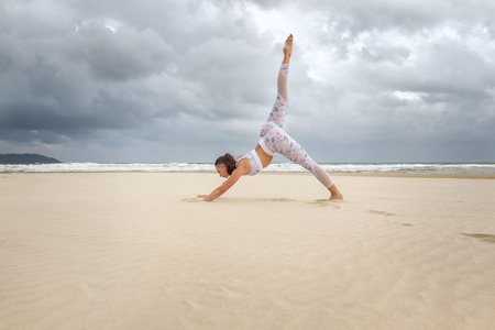 Young beautiful woman practice yoga on sea sand at daytime Stock Photo