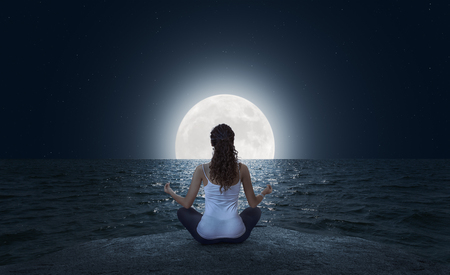 Young woman meditating in Lotus pose on the sea beach at full moon night Stock fotó