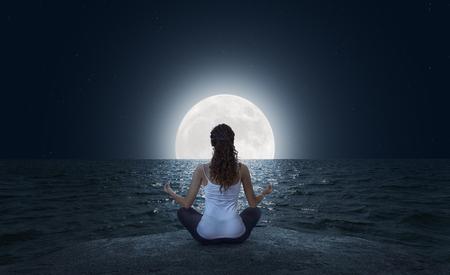 Young woman meditating in Lotus pose on the sea beach at full moon night Фото со стока