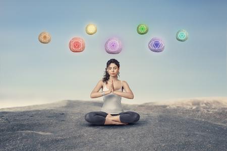 Young woman levitating stones with chakra symbols during outdoor yoga meditation Foto de archivo