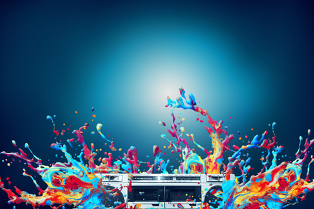 Abstract colorful paint splash with vintage stereo cassette player over blue background Standard-Bild