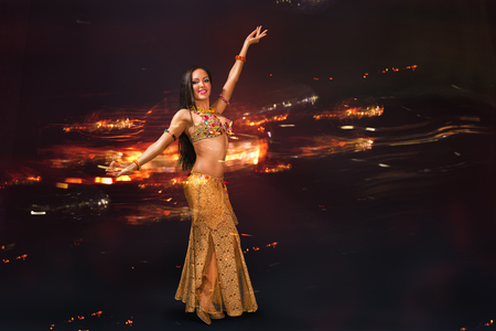 Young woman doing belly dance performance in exotic costume with abstract background behind her Foto de archivo